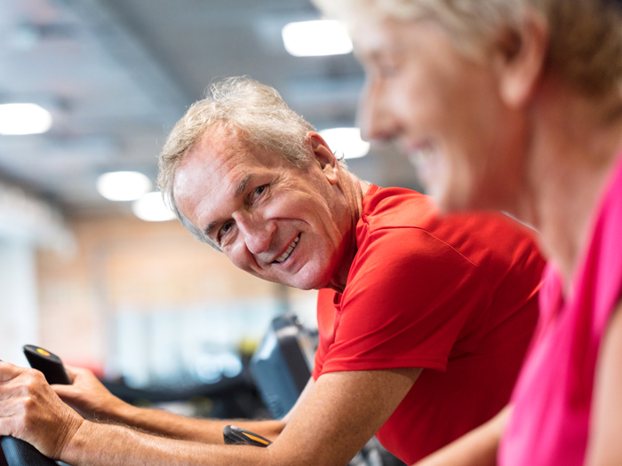 older man on exercise machine smiling at person next to him